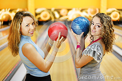 Two women hold balls and smile in bowling club