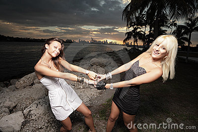 Two women holding hands and swinging