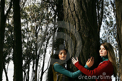 Two women hugging a tree