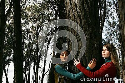 Two women hugging a tree
