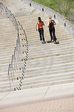Two women jogging up steps
