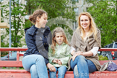 Two women and little girl sit on bench