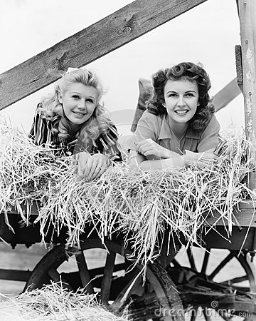 Free Two Women Lying In A Wagon Of Hay With Their Legs In The Air Stock Photography - 52015132