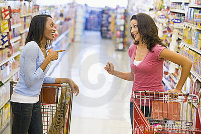 Two women meeting in supermarket