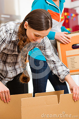 Two women with moving box in her house