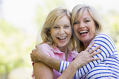Two women outdoors hugging and smiling