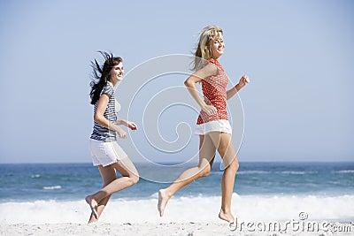 Two women running along beach