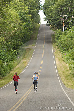 Two women running on rural road