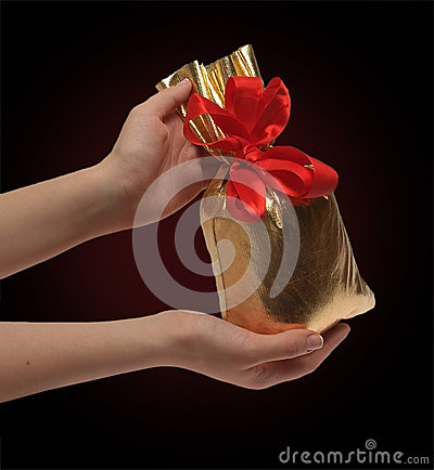 Two women s hands are holding a bag of gifts