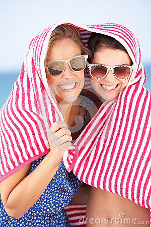 Two Women Sheltering From Sun On Beach Holiday