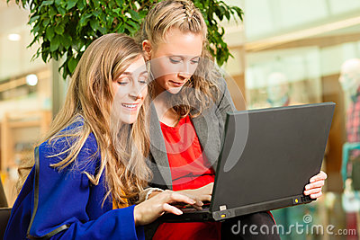 Two women shopping in mall with laptop
