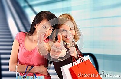 Two women shopping, thumbs up
