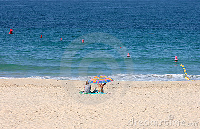 Two women sitting under parasol on sandy beach