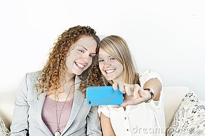 Two women taking photo with phone