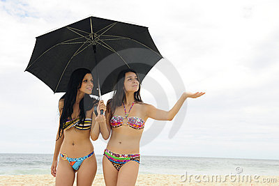 Two women with umbrella on the beach