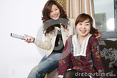 Two women watch TV