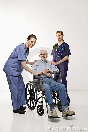 Two women wearing scrubs with elderly man in wheelchair.