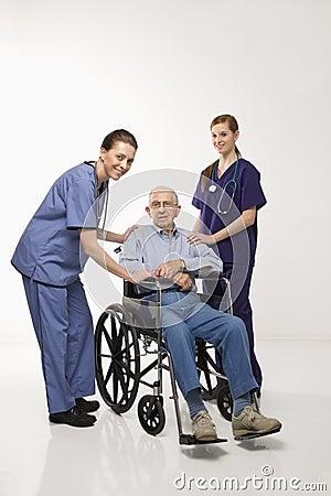 Free Two Women Wearing Scrubs With Elderly Man In Wheelchair. Royalty Free Stock Image - 2042536