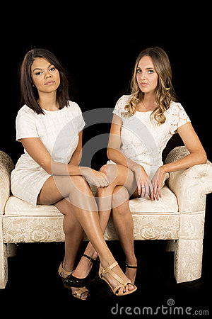 Two Women White Dress On Black Facing Legs Crossed Stock