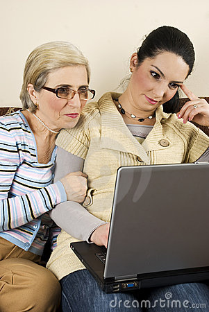 Two women work on laptop home