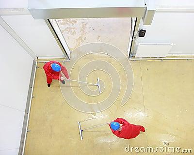 Two workers cleaning floor in industrial building
