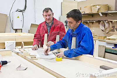 Two workers at a wooden workbench