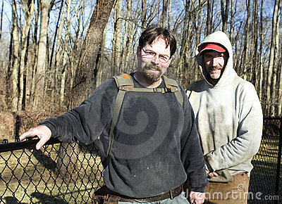 Two workmen repairing chain link fence