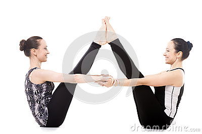 two yogi female partners in balancing stick yoga pose