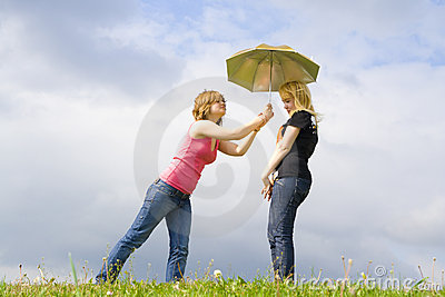 The two young attractive girls with a umbrella