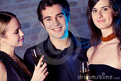 Two young attractive sweet women and man with champagne glasses
