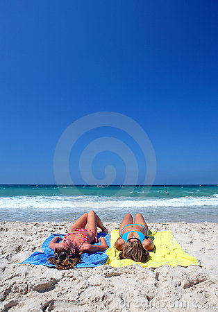 Two young attractive women chilling in the sun on holiday or vac