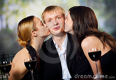 Two young attractive women kissing man with red-wine glasse