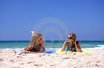 Two, young, attractive women lying on a beach
