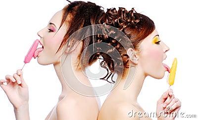 Two  young beautiful girls eating sweet ice-cream