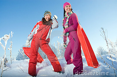 Two young beautiful girls with sledges