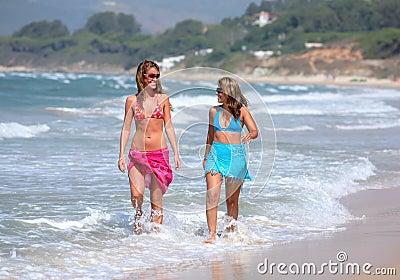 Two young beautiful tanned women walking along sandy beach