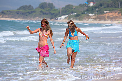 Two young beautiful tanned women walking along sandy beach
