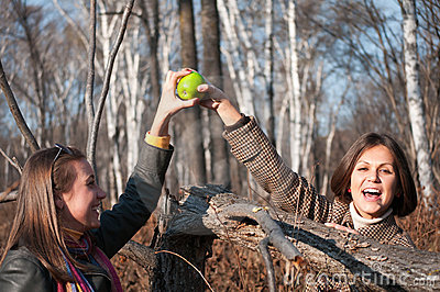 Two young beautiful women playing with apple