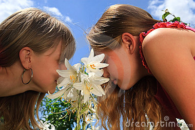Two young blond girls behind white lily