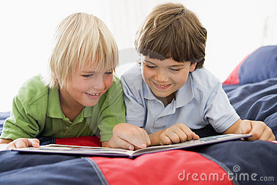 Two Young Boys Lying Down On A Bed Reading A Book
