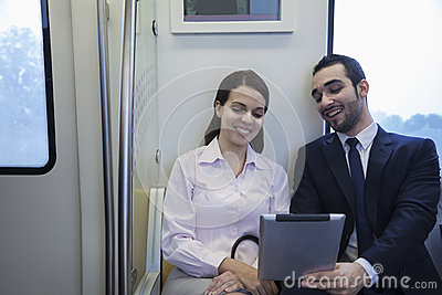 Two young business people sitting and looking at a digital tablet on the subway