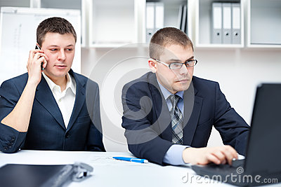 Two young businessmen working together at office