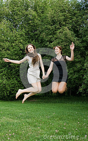 Two young cheerful women jumping