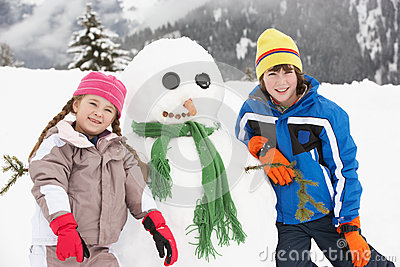 Two Young Children Building Snowman On Ski Holiday