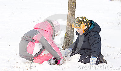 Two young children digging in the snow