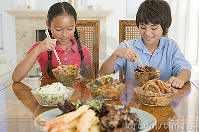 Two young children eating chinese food