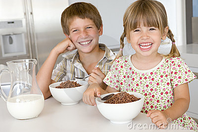 Two young children in kitchen eating cereal