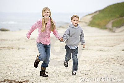 Two young children running on beach