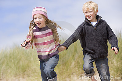 Two young children running on beach holding hands