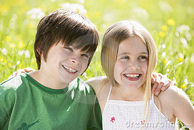 Two young children sitting outdoors arm in arm